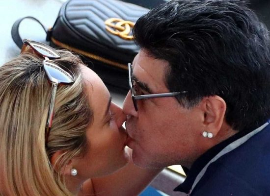 Ao lado da namorada, Maradona fica comportado após desclassificação da Argentina